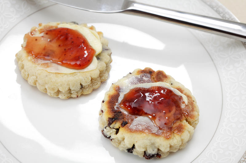 Welsh cakes with strawberry jam. Small homemade Welsh cakes, a traditional griddle-pan baked scone, served with butter and jam royalty free stock photo