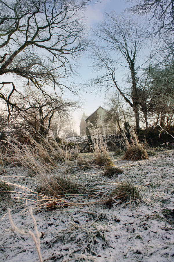 Welsh Hill Farm In Winter. A Welsh Hill farm viewed from a neighbouring field in winter. A thin layer of ice and snow covers the ground and the long grasses are stock photo