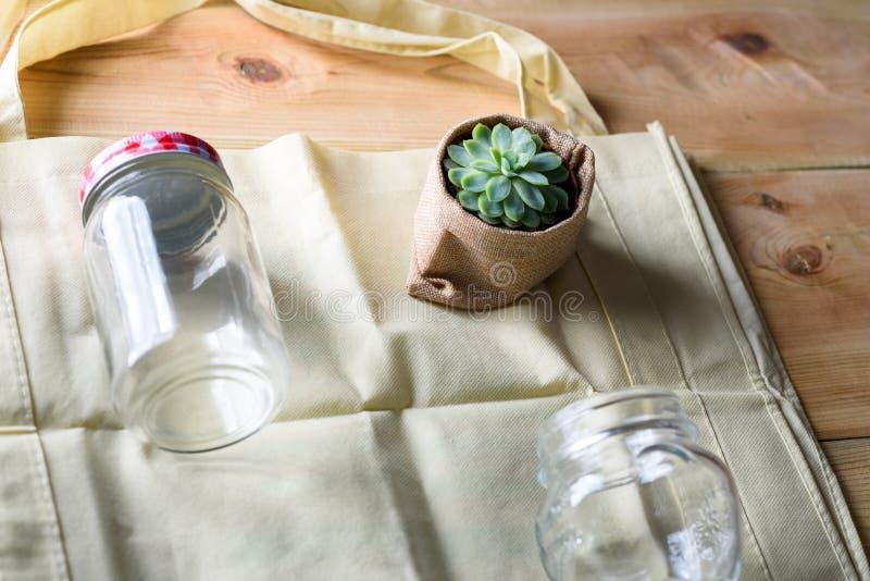Welt frei vom Plastik Grüne Produkttasche gemacht vom Bambus oder von der Wiederverwendung, saftig und Glasgefäß auf Naturholzhin stockfoto