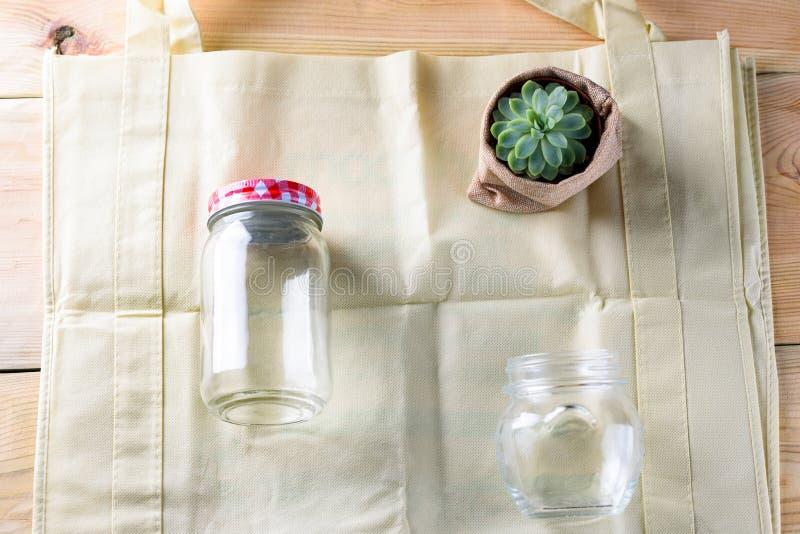 Welt frei vom Plastik Grüne Produkttasche gemacht vom Bambus oder von der Wiederverwendung, saftig und Glasgefäß auf Naturholzhin stockfotos