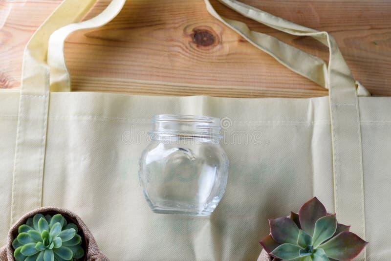 Welt frei vom Plastik Grüne Produkttasche gemacht vom Bambus oder von der Wiederverwendung, saftig und Glasgefäß auf Naturholzhin stockfotografie