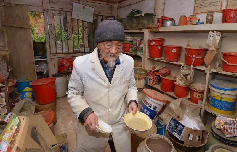Weltberühmter Kräuterdoktor Ho, das traditionelle Kräutermedizin vorbereitet stockbild