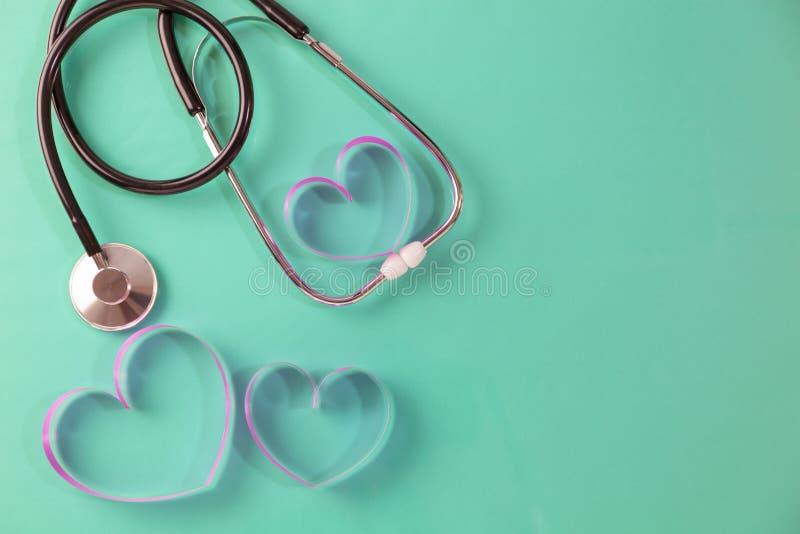 Weltgesundheitstageshintergrund, Stethoskop und rosa Bandherz auf grünem Hintergrund, Konzeptgesundheitswesen und medizinischem H stockbild