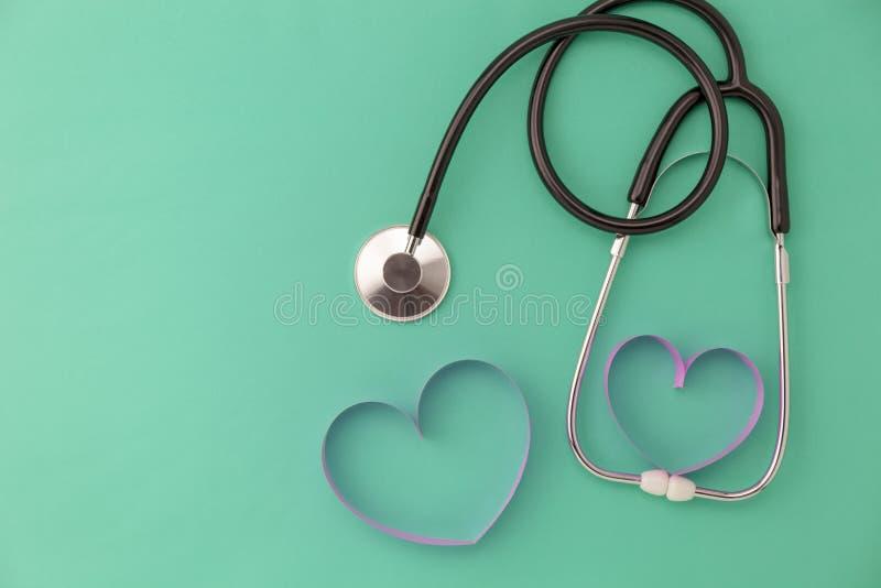 Weltgesundheitstageshintergrund, Stethoskop und rosa Bandherz auf gr?nem Hintergrund, Konzeptgesundheitswesen und medizinischem H lizenzfreie stockbilder