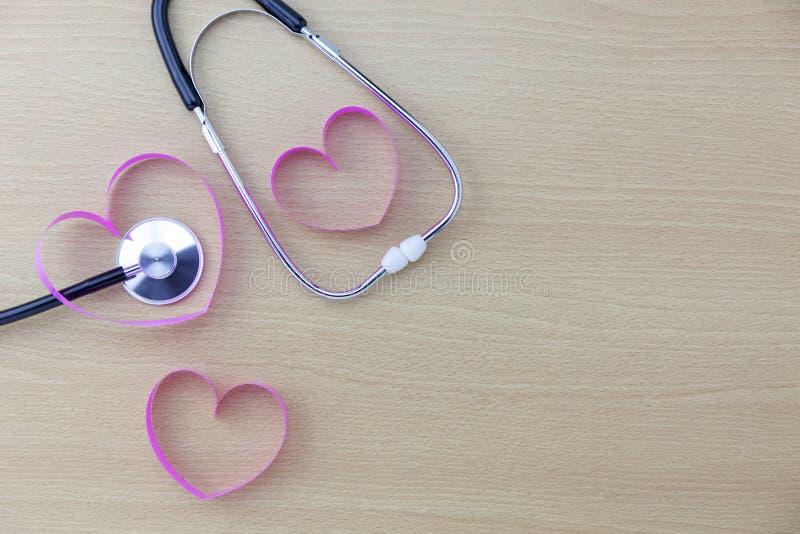 Weltgesundheitstageshintergrund, Stethoskop und rosa Bandherz auf hölzernem Hintergrund, Konzeptgesundheitswesen und medizinische lizenzfreie stockfotos