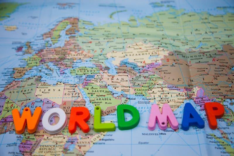 Weltkarte geschrieben mit Bauklötzen auf eine Weltkarte lizenzfreie stockfotografie
