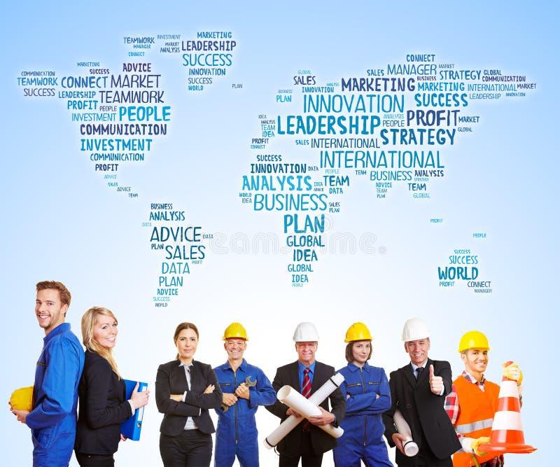 Weltkarte hinter Arbeitskräften und Ingenieuren zusammen lizenzfreie stockbilder