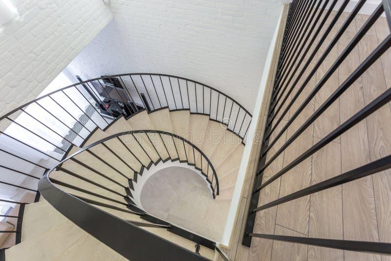 Wendeltreppe im hellen Innenraum mit weißer Backsteinmauer in der teuren Wohnung der Auslese lizenzfreies stockbild