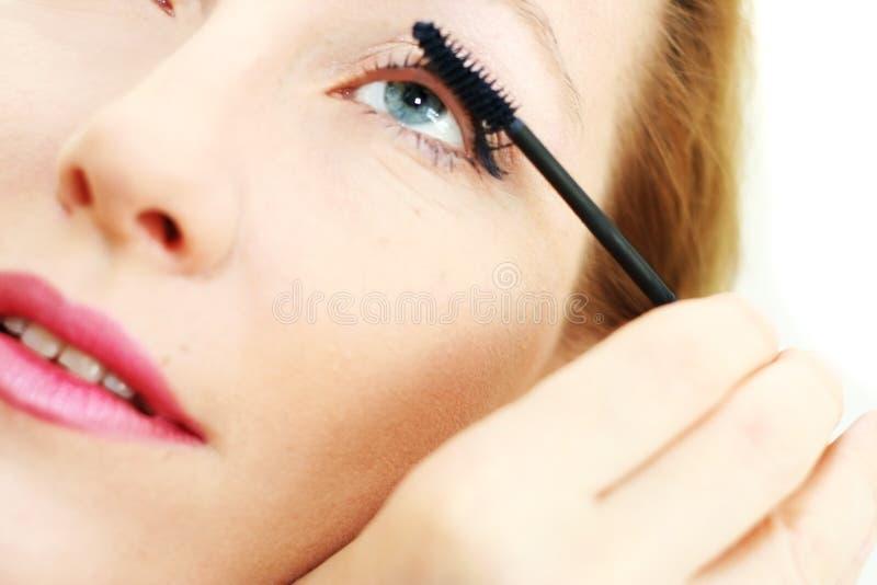 Wenden Sie Wimperntusche auf blauem Auge an lizenzfreies stockbild