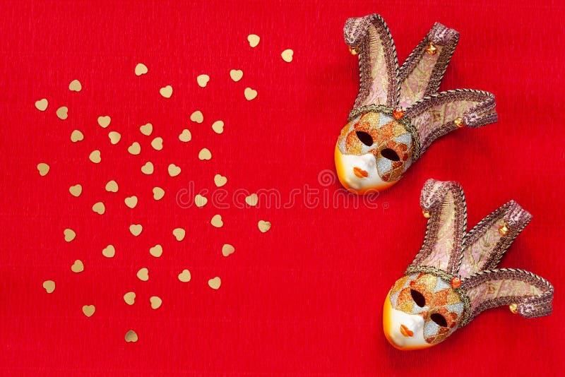 Weneckie maski z kierowego kształta błyskotliwości złocistymi confetti Odgórny widok, zakończenie na w górę czerwonego tła fotografia stock