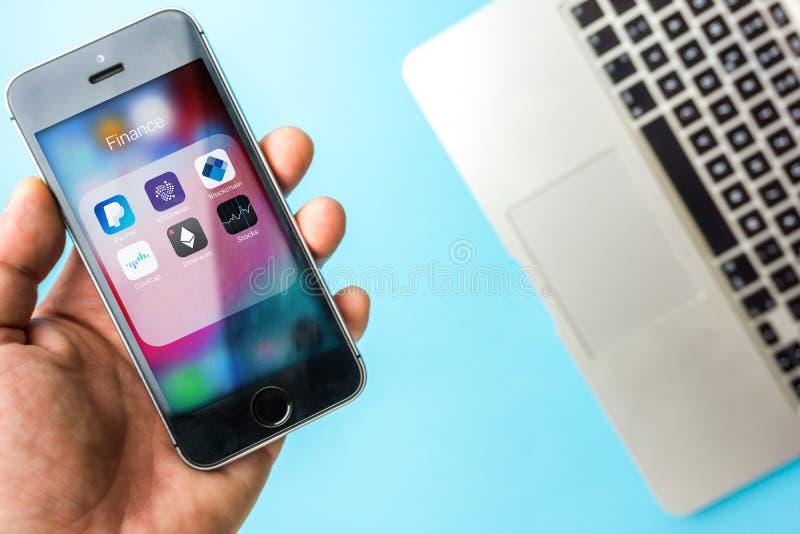 Wenen Oostenrijk Maart 20 2019, SE van de appeliphone van de Handholding met Diverse financiële apps in omslag tegen blauw bureau stock foto