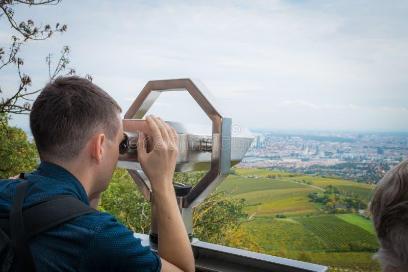 WENEN, OOSTENRIJK - OKTOBER 10, 2018: Een mens bekijkt aard en stad door verrekijkers bij de herfst in Wenen Oostenrijk royalty-vrije stock afbeelding