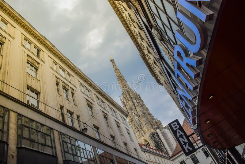 Wenen, Oostenrijk - September, 15, 2019: De Voorgevel van een Winkelcomplex, een bank en een de Kathedraaltoren van Wenen bij stock foto