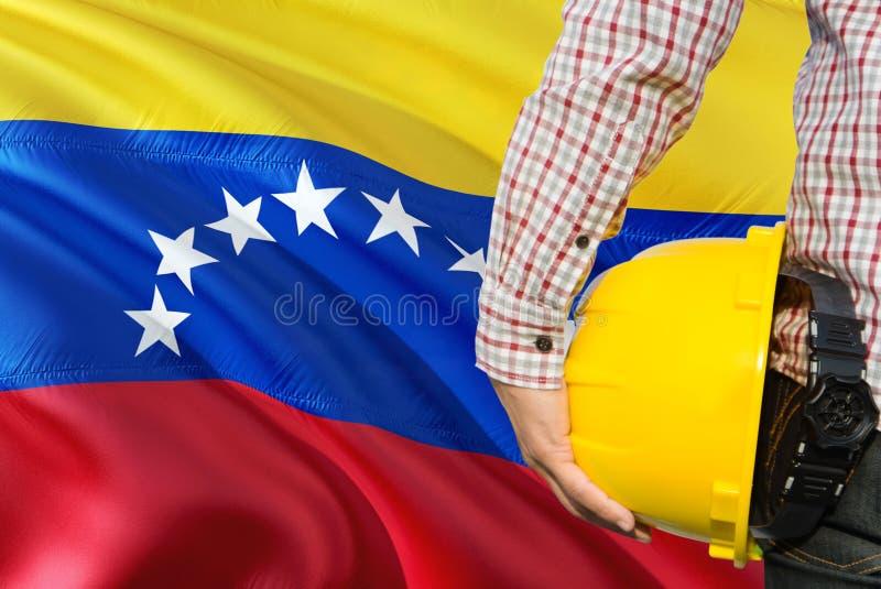 Wenezuelski inżynier trzyma żółtego zbawczego hełm z machać Wenezuela chorągwianego tło Budowy i budynku poj?cie zdjęcia royalty free