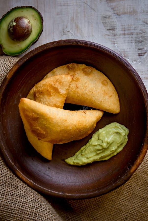 WENEZUELSKI KOLUMBIJSKI jedzenie Wenezuelski kolumbijski typicals śniadanie - kukurydzani empanadas z mięsem w glinianym pucharze zdjęcie royalty free