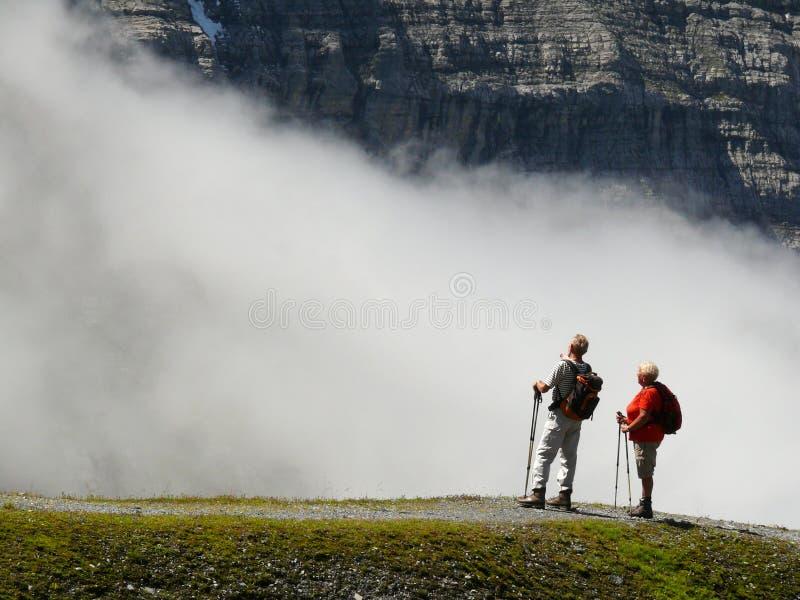 Wengen Schweiz 08/17/2010 Tv? fotvandrare i de h?ga bergen beundrar landskapet royaltyfri bild