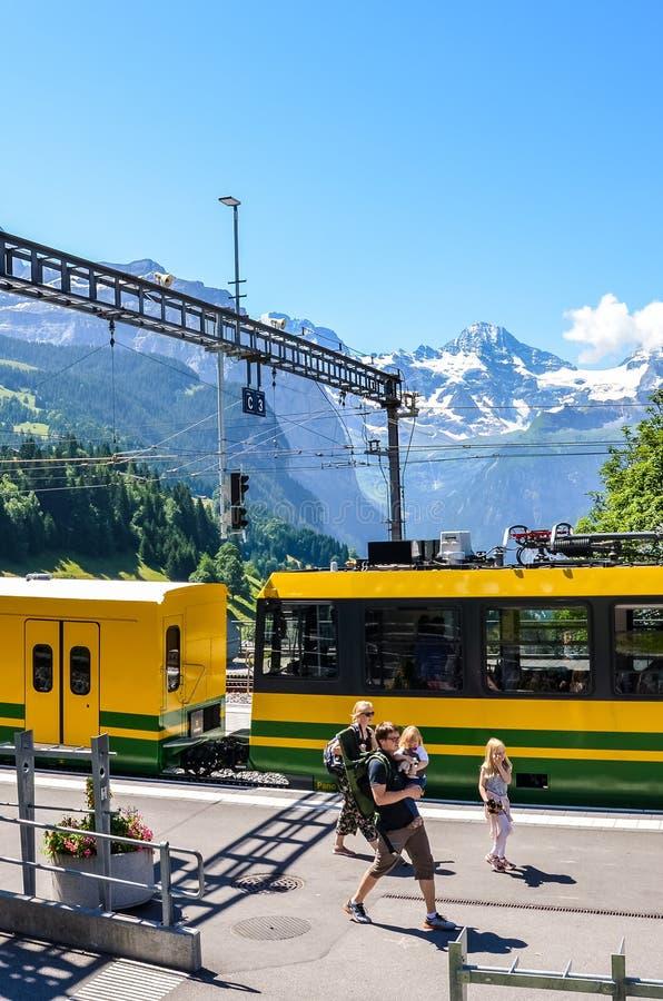 Wengen Szwajcaria, Lipiec, - 16 2019: Rodzina na wycieczki odprowadzeniu na platformie w magistrala pociągu statio Piękni Alps z  obrazy stock