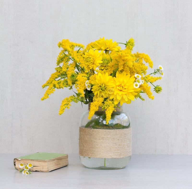 Wenig altes Buch, ein Blumenstrauß von Blumenchrysanthemen, Goldrute und Gänseblümchen in einem Glasvase selbst gemacht lizenzfreies stockfoto