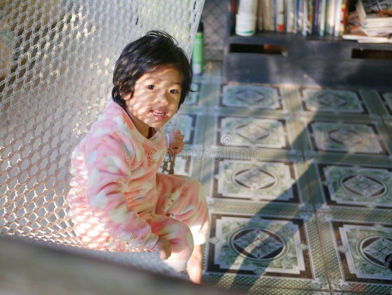 Wenig asiatisches Baby, das bequem sich auf einer Hängematte mit dem Morgensonnenlicht hinsetzt stockbilder