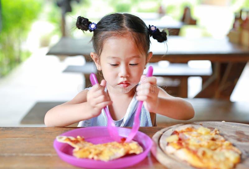 Wenig asiatisches Kind, das auf dem Tisch Pizza isst lizenzfreie stockbilder