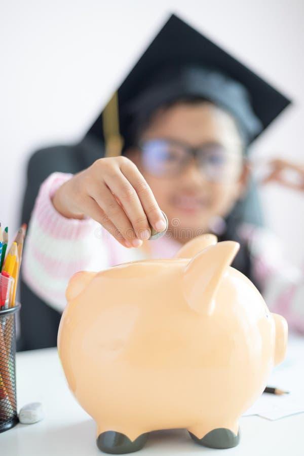 Wenig asiatisches Mädchen, welches die Münze in Sparschwein und in Lächeln mit Glück für das Geld in der Zukunft speichert zum we lizenzfreies stockbild