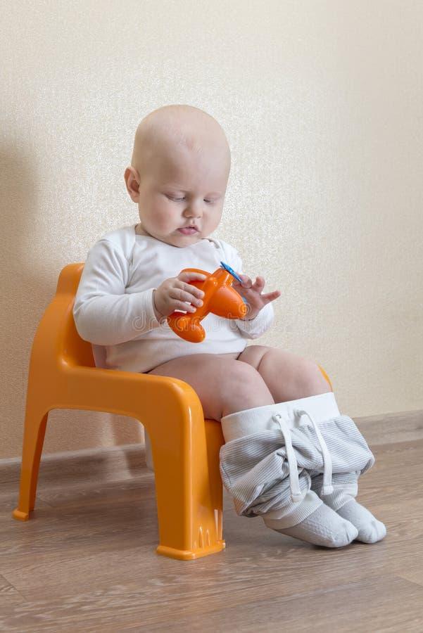Wenig Baby, das auf dem Topf sitzt und mit Spielzeugflugzeug spielt stockbilder