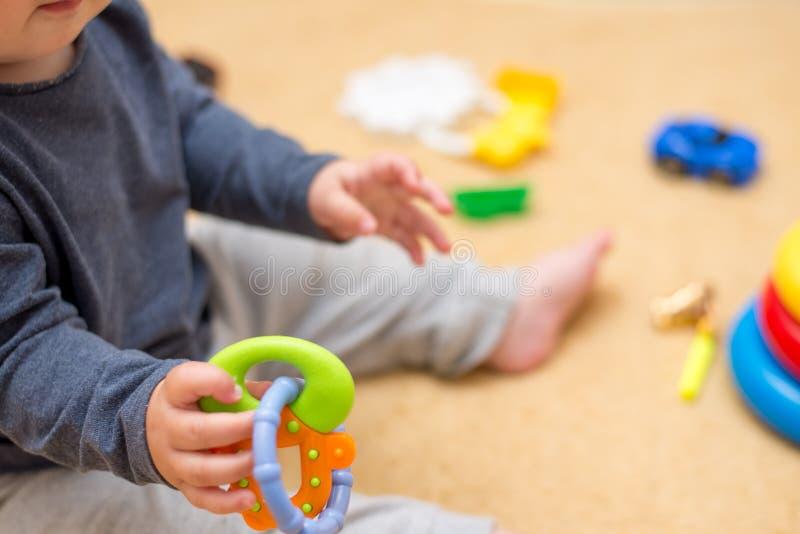 Wenig Baby, das mit vielen bunten Spielwaren auf Boden im Raum spielt stockfoto