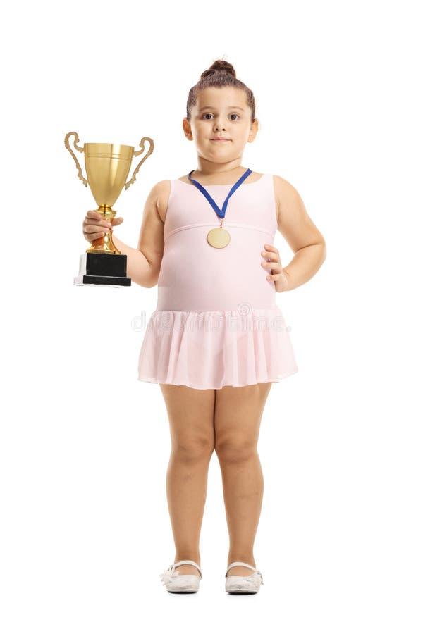 Wenig Ballerinamädchen, das eine Goldtrophäenschale und eine Medaille hält stockbild