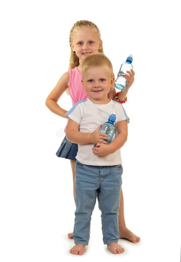 Wenig barfüßigjungenstände nahe bei reizend Mädchen und Flasche Wasser in den Händen lokalisiert auf Weiß lizenzfreies stockbild