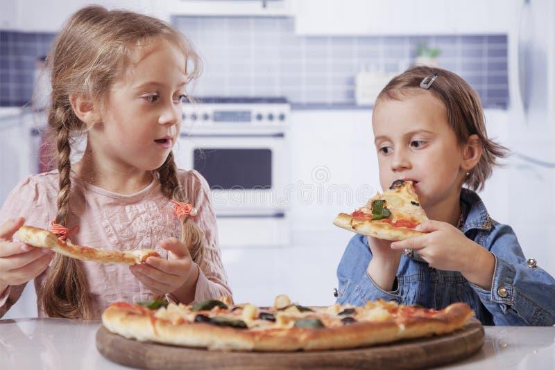 Wenig Beste Freunde des netten Kindermädchens, die ein Pizzastück essen Nahrung, glückliches Kindheitskonzept stockfotografie