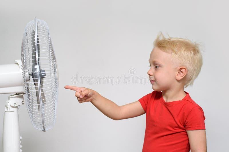 Wenig blonder Junge in einem roten T-Shirt ber?hrt den Fan mit seinem Finger Seashells gestalten auf Sandhintergrund stockfoto