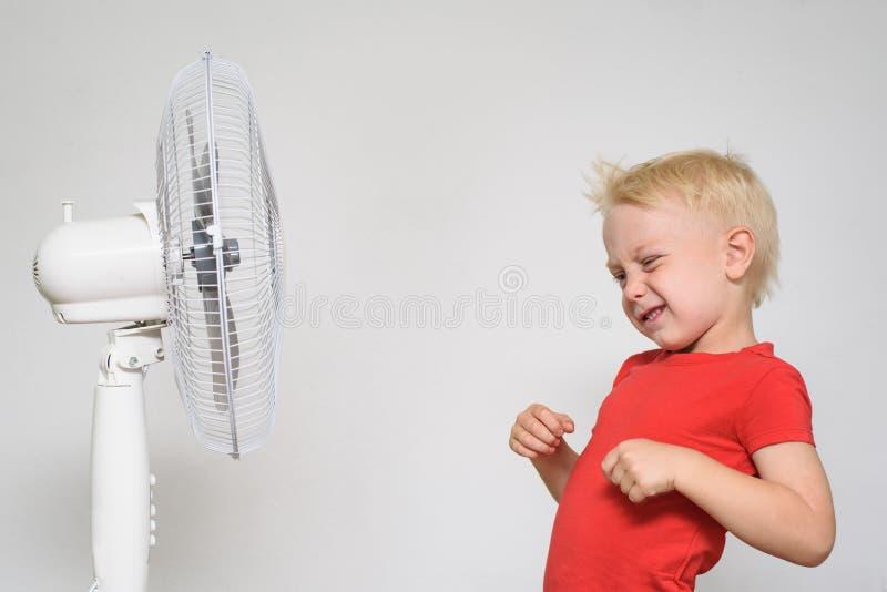 Wenig blonder Junge in einem roten T-Shirt macht ein Gesicht nahe dem Fan Seashells gestalten auf Sandhintergrund stockbild