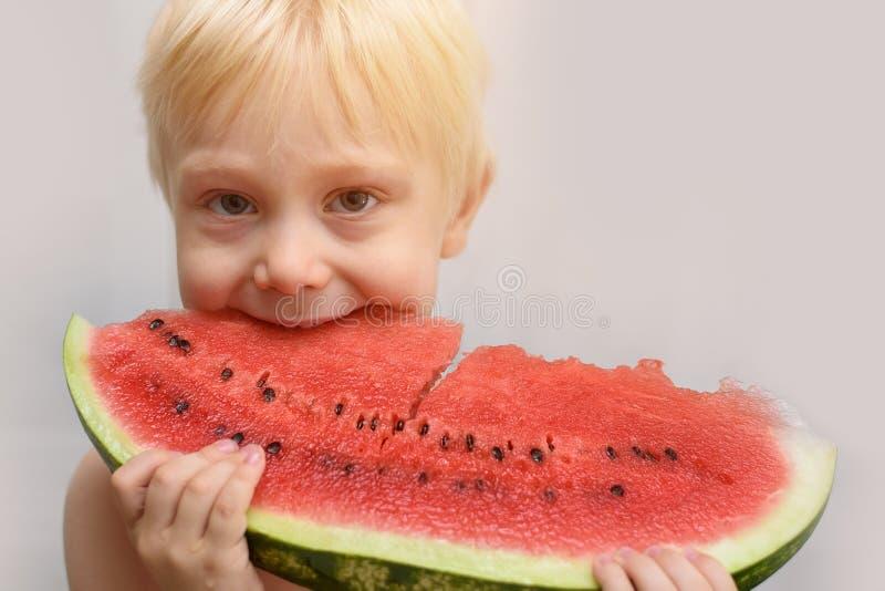 Wenig blonder Junge isst Menge Wassermelone Seashells gestalten auf Sandhintergrund Wohnzimmer konzipiert in der Retro- Art lizenzfreies stockbild