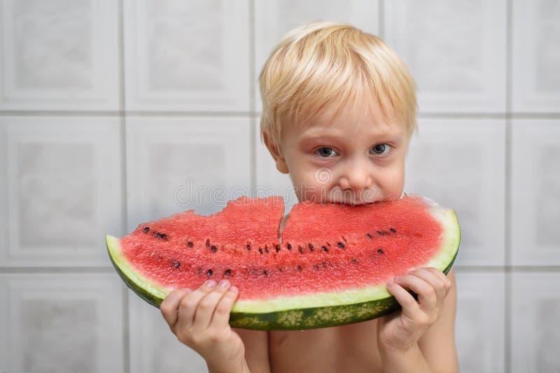 Wenig blonder Junge isst Menge Wassermelone Seashells gestalten auf Sandhintergrund Wohnzimmer konzipiert in der Retro- Art stockbild