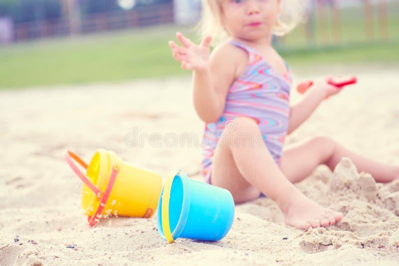 Wenig blondes Baby, das mit Sand auf dem Strand unter Verwendung der Plastikspielwaren spielt lizenzfreies stockbild