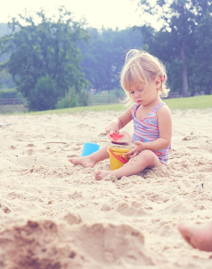 Wenig blondes Baby, das mit Sand auf dem Strand unter Verwendung der Plastikspielwaren spielt lizenzfreie stockfotos