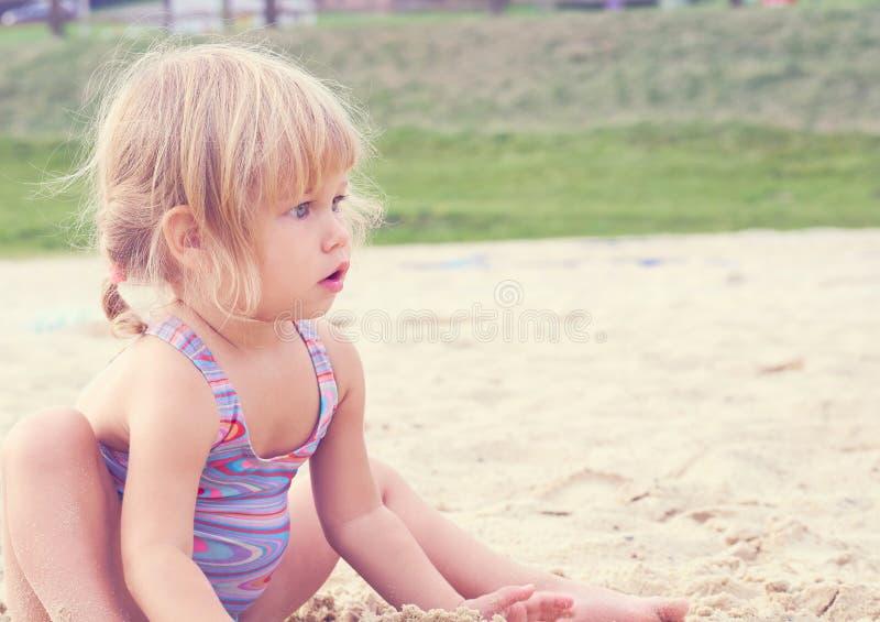 Wenig blondes Baby, das mit Sand auf dem Strand unter Verwendung der Plastikspielwaren spielt stockfoto