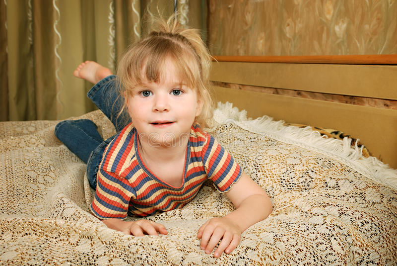 Wenig blondes lächelndes Mädchenlügen lizenzfreies stockfoto