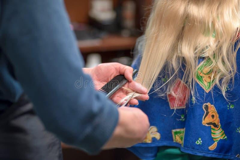 Wenig blondes Mädchen, das Haarordnung erhält stockfoto