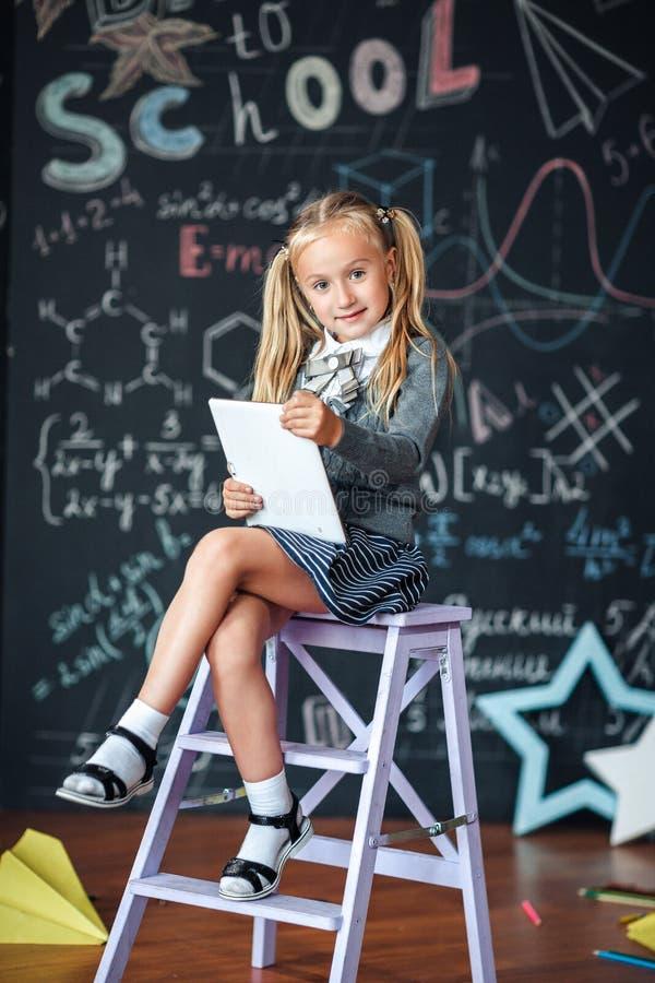 Wenig blondes Mädchen in der Schuluniform, die weißen Tabletten-PC im Chemieunterricht hält Tafel mit Schulformelhintergrund stockbilder