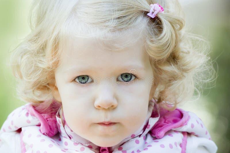 Wenig blondes Mädchen des gelockten Haares mit den geschürzten Lippen stockfoto