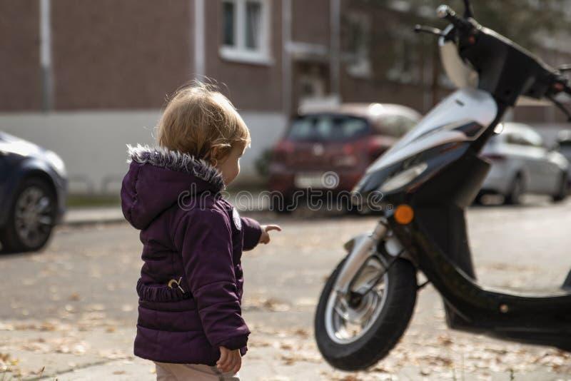 Wenig blondes Mädchen zeigt einen Finger auf einem Bewegungsroller im afte stockfotos