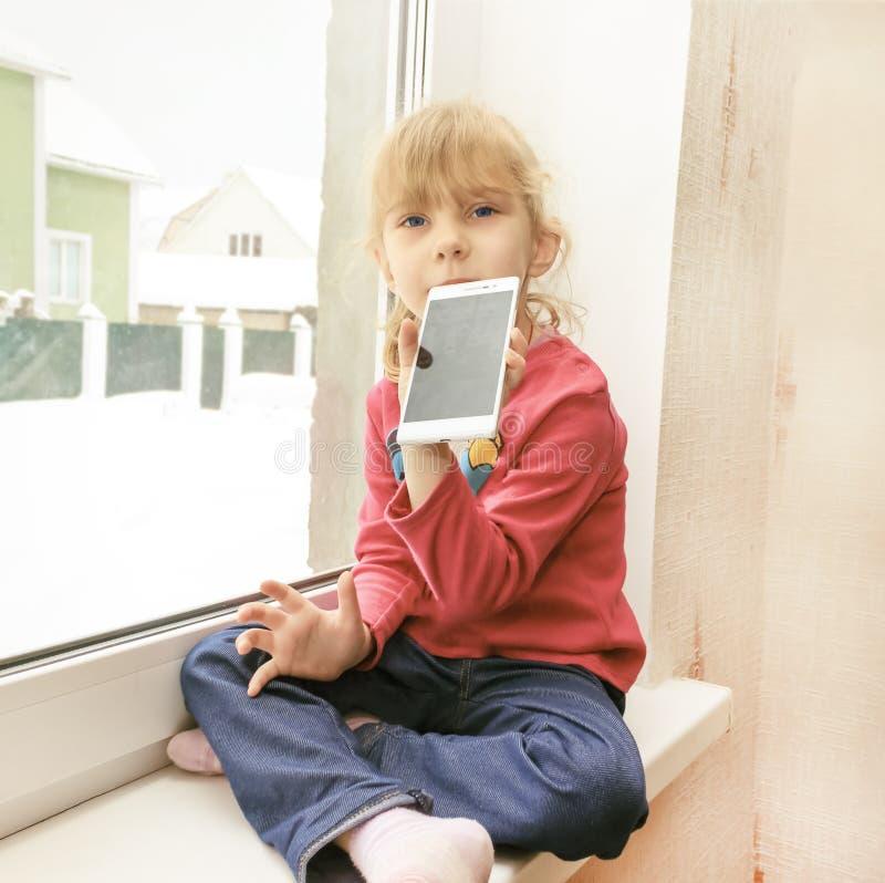 Wenig blondes Sitzen auf Fensterbrettern nahe Fenster, mit Telefon in der Hand lizenzfreie stockfotografie