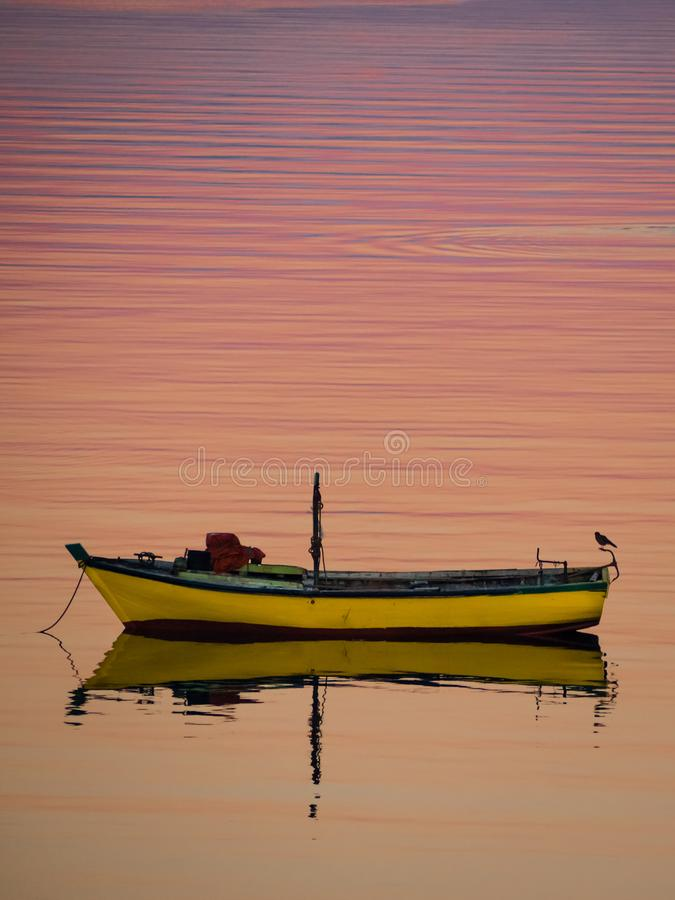 Wenig Boot, das auf das ruhige Wasser unter erstaunlichen Sonnenuntergang in Quellon, Chiloe-Insel in Chile schwimmt lizenzfreies stockbild