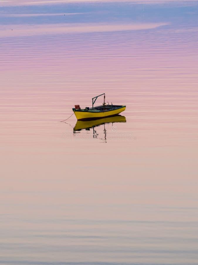 Wenig Boot, das auf das ruhige Wasser unter erstaunlichen Sonnenuntergang in Quellon, Chiloe-Insel in Chile schwimmt lizenzfreie stockfotografie