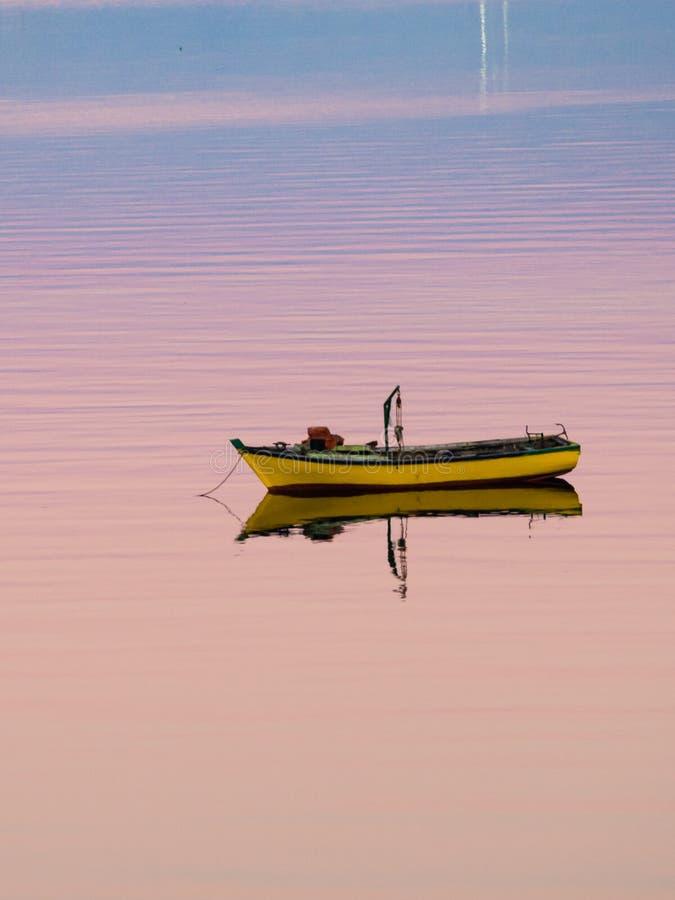 Wenig Boot, das auf das ruhige Wasser unter erstaunlichen Sonnenuntergang in Quellon, Chiloe-Insel in Chile schwimmt lizenzfreies stockfoto