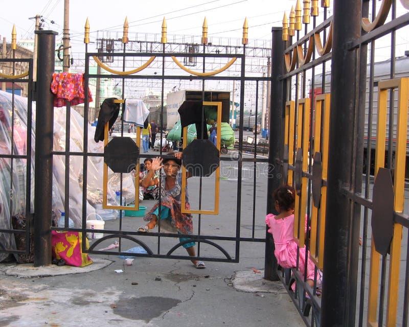 Wenig braunes Straßenmädchen schaut heraus durch die Stangen des Zauns lizenzfreies stockbild