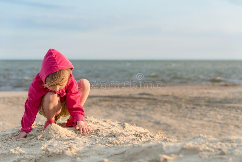 Wenig drei Jahre alte Mädchen, die im Sand auf dem See-Strand, Sonnenuntergang und wenig Brise und, Sommerferien, Kind-developmen lizenzfreie stockfotografie