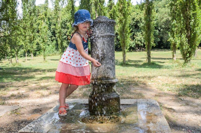 Wenig entzückendes Baby trinkt Wasser vom Trinkbrunnen der römischen Nase auf den Straßen von Rom stockbilder