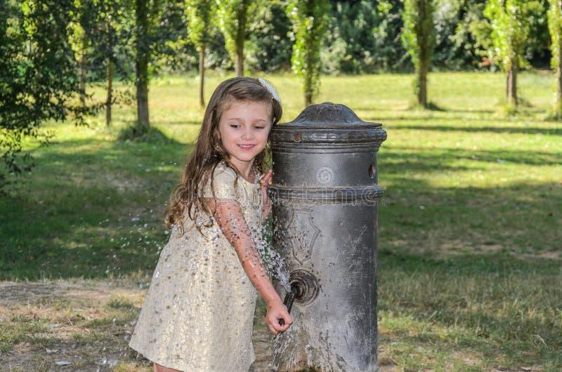 Wenig entzückendes Baby trinkt Wasser vom Trinkbrunnen der römischen Nase auf den Straßen von Rom lizenzfreies stockbild